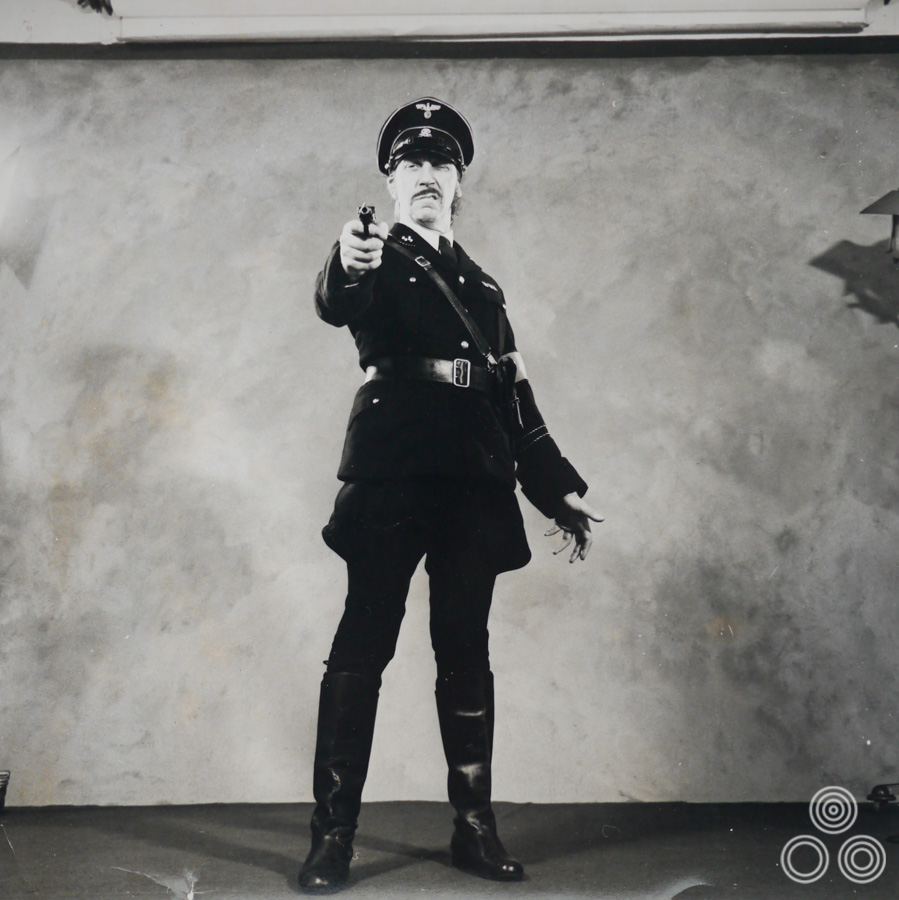 Tom Chantrell poses in a Nazi uniform in one reference shot from a sequence that would be used by him to paint the quad for the unmade Hammer Studios film The Savage Jackboot, 1972. See here for more details.
