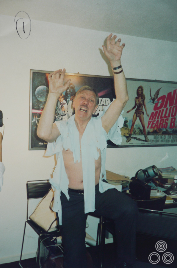Tom Chantrell poses with a torn shirt in a reference pose that he would later use to paint one of his posters or video covers, circa 1986.