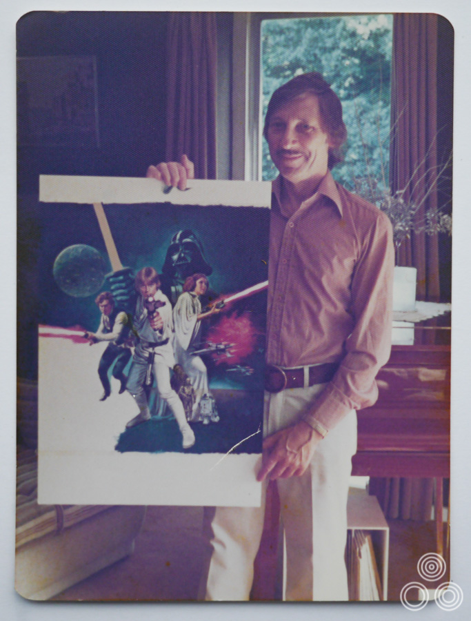 Tom Chantrell stands holding the near-finished artwork for Star Wars, arguably his most famous work. Photo taken by his wife Shirley in 1977.