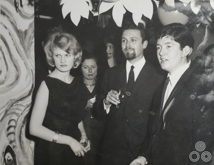 Vic Fair (centre) stands with colleagues, including Richard Vaughan (right) and David Till (behind Vic), at a party, circa 1964.