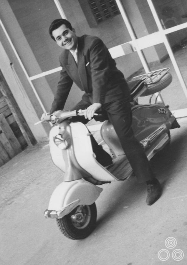 Renato Casaro sits astride a Vespa in Rome, circa 1965.