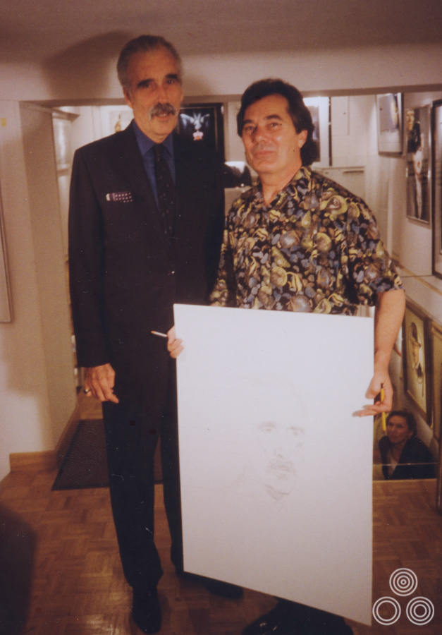 Renato Casaro stands next to an imposing Christopher Lee holding a sketch the artist had made of the legendary British actor, circa 1997.