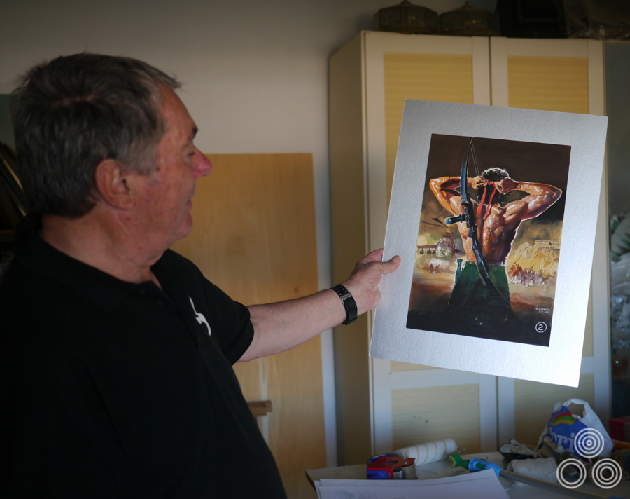 Renato Casaro stands with a coloured concept painting for Rambo III that he painted for the film in 1988. Photo taken in 2013.