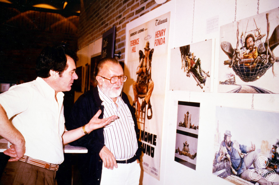 Renato Casaro stands with Sergio Leone talking about his work for the film 'My Name is Nobody', circa 1984