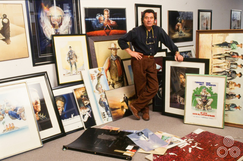 Renato Casaro stands with a large selection of his own work, framed and ready to display as part of an exhibition, circa 1998