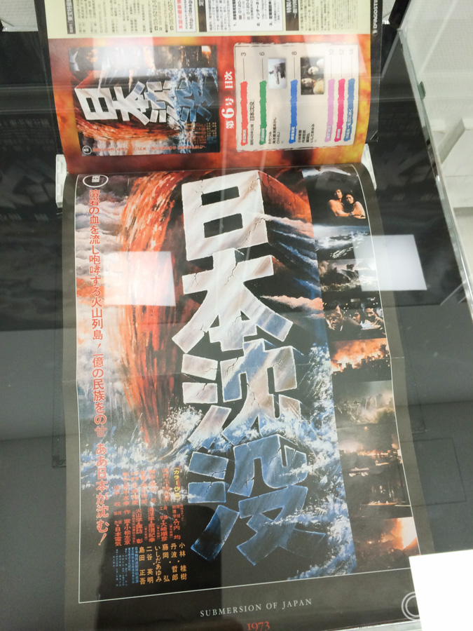 A display case containing a printed copy of Ohrai's very first film poster for the original Japan Sinks (Nihon Chinbotsu) that was done in 1973