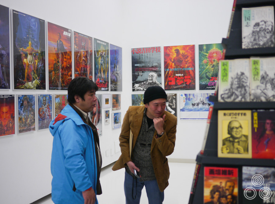 Exhibition director Tatsuya Ishida (left) and my friend, and fellow collector, Toru Onozato examine some of the many book covers painted by Ohrai in the first room of the exhibition.